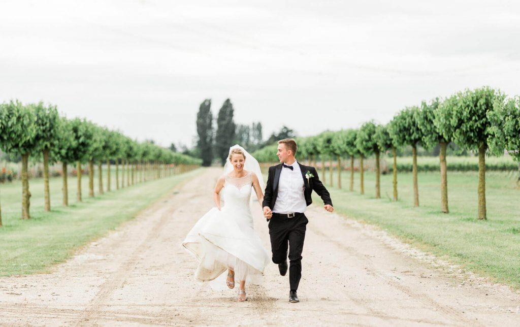 Groom and bride running through vineyard in the rain | West Sussex wedding photographer