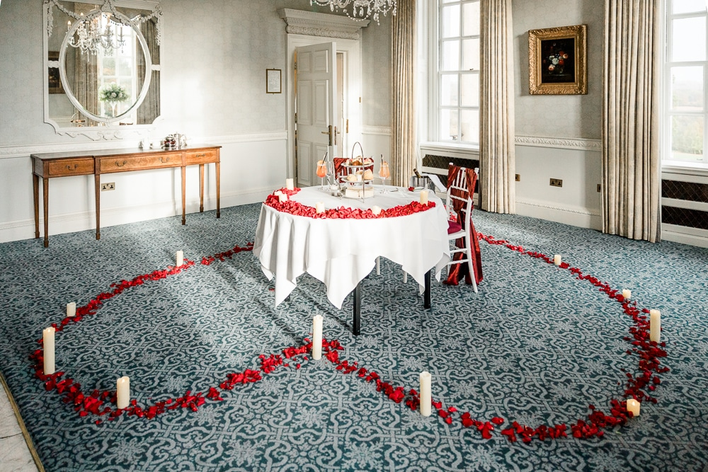 Proposal at Buxted Park Hotel in private room filled with red rose petals