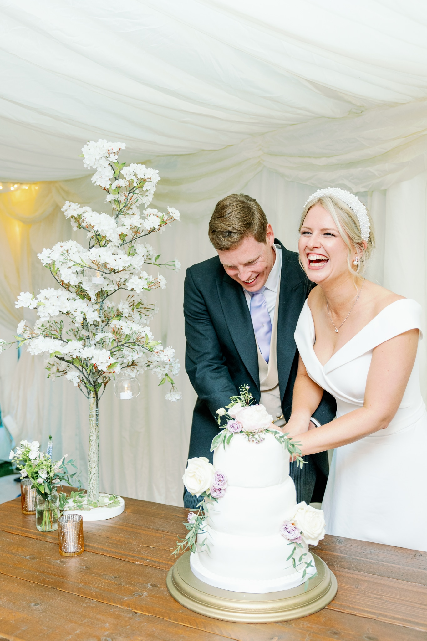 Couple cutting cake in marquee in East Sussex