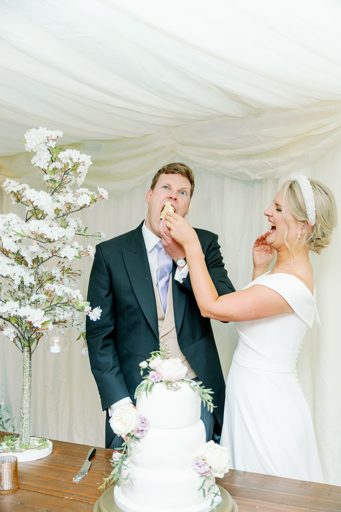 Groom eating wedding cake in marquee in Rye