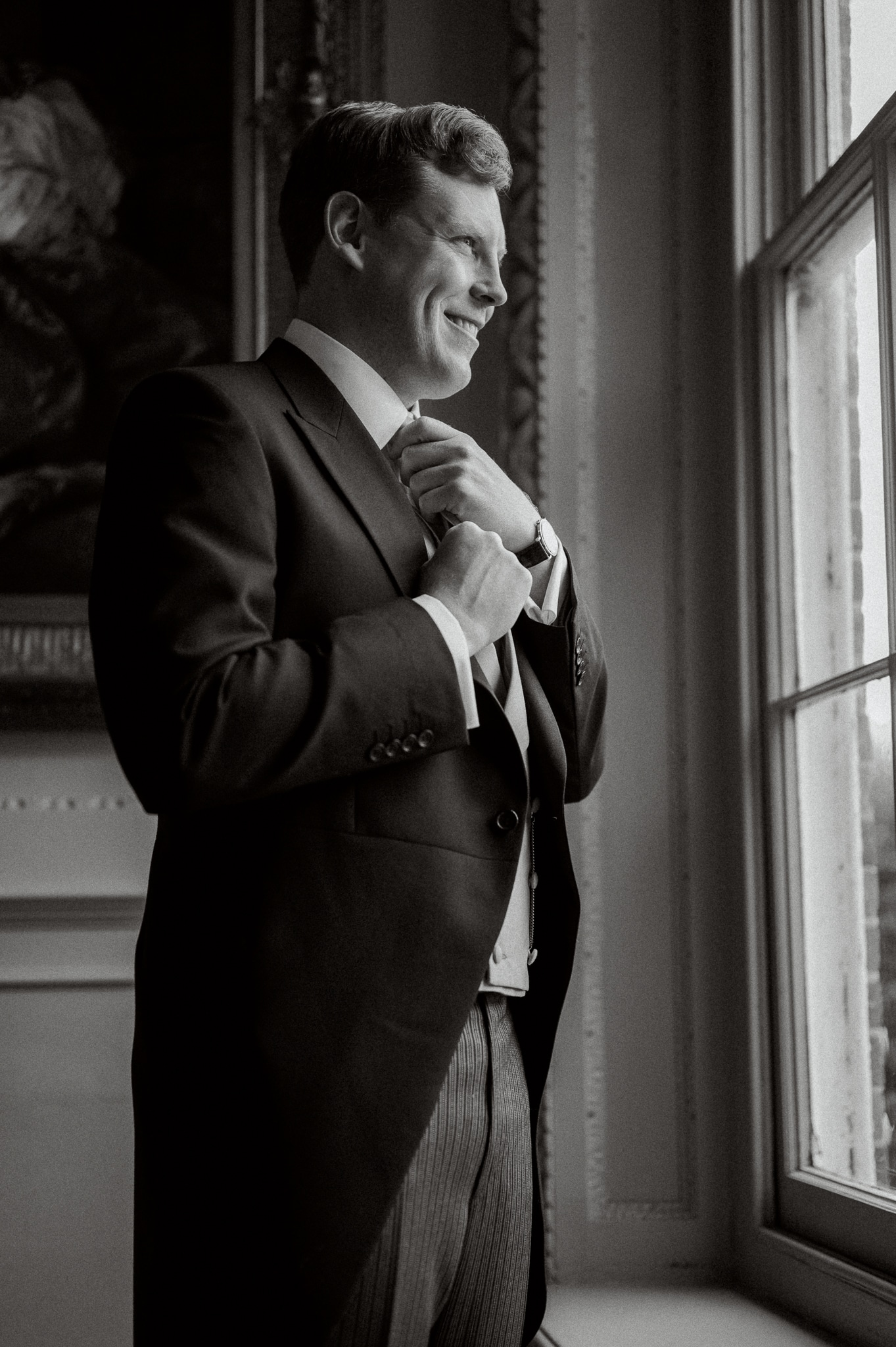 Groom on stairs at Brickwall House with East Sussex wedding photographer