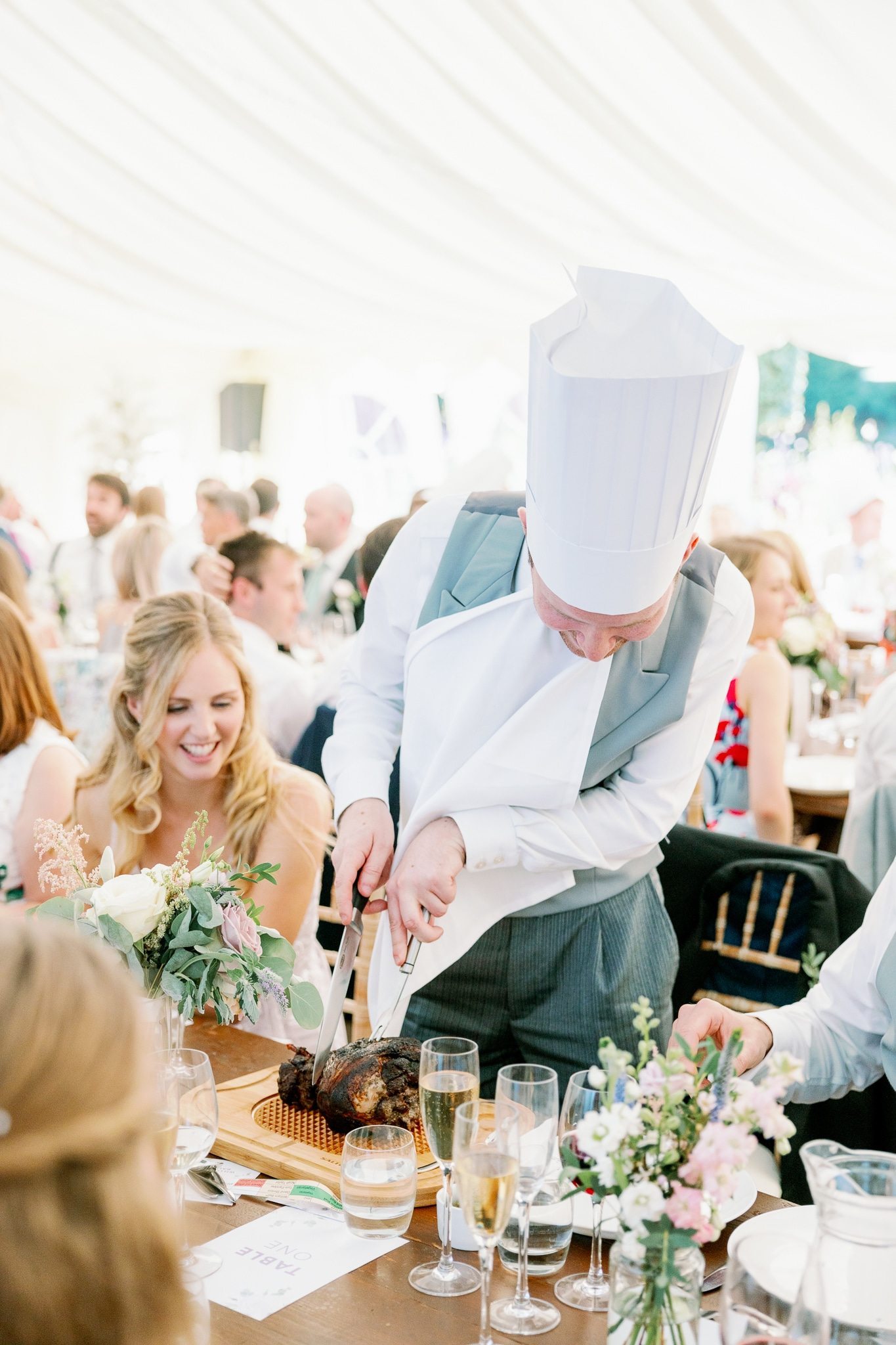 Wedding breakfast guests carve meat in chief hats